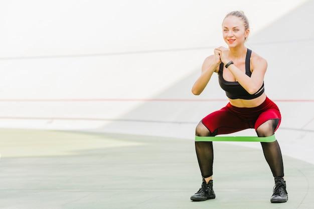 Vrouw die oefeningen met elastiekje doet Gratis Foto