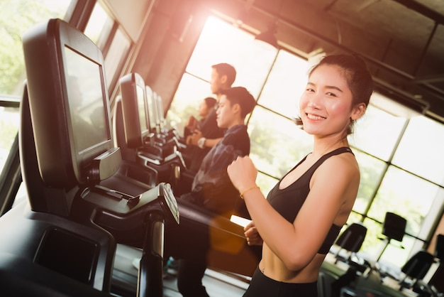 Vrouw die of op tredmolens in moderne sportgymnastiek loopt jogt. oefening concept. Premium Foto