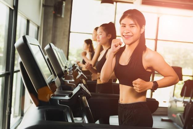 Vrouw die of op tredmolens in moderne sportgymnastiek loopt jogt. oefening en sportconcept. Premium Foto