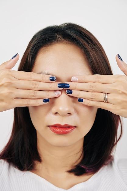 Vrouw die ogen behandelt met handen Premium Foto