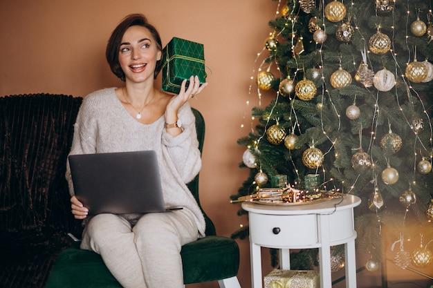 Vrouw die online op kerstmisverkoop winkelt Gratis Foto