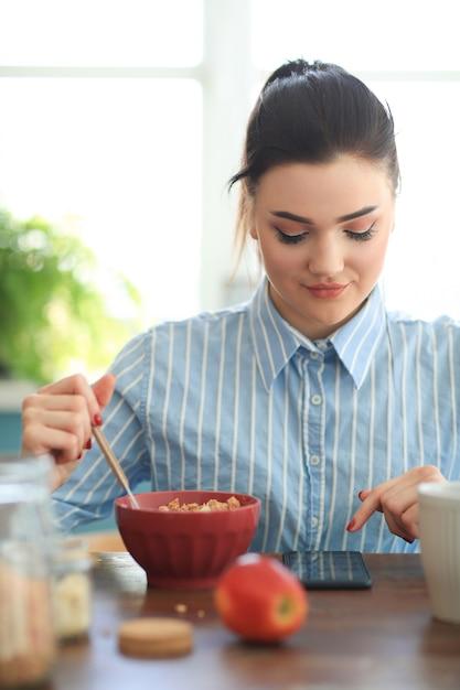 Vrouw die ontbijt heeft terwijl het babbelen met haar telefoon Gratis Foto