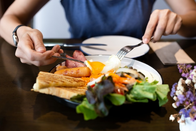 Vrouw die ontbijt met gebraden eieren, worsten, groente en toost heeft. Premium Foto