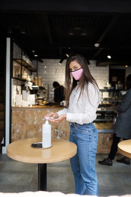 Vrouw die ontsmettingsgel gebruikt, reinigt de handen van het coronavirusvirus in het café Gratis Foto