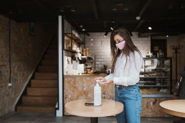 Vrouw die ontsmettingsgel gebruikt, reinigt handen van coronavirusvirus in café. Gratis Foto