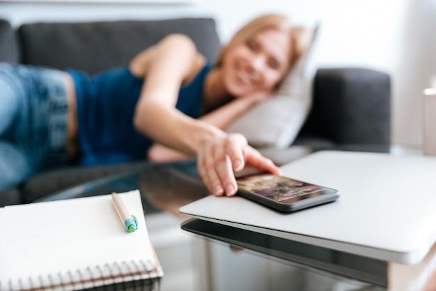 Vrouw die op bank ligt en mobiele telefoon van lijst neemt Gratis Foto