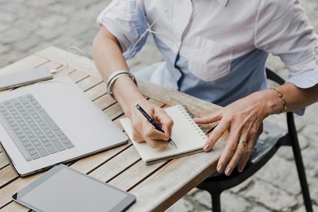 Vrouw die op de mening van de notitieboekje hoge hoek schrijft Gratis Foto