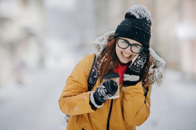 Vrouw die op de telefoon spreekt en koffie drinkt. vrouw die in de winter loopt strrt en op de mobiele telefoon spreekt Premium Foto