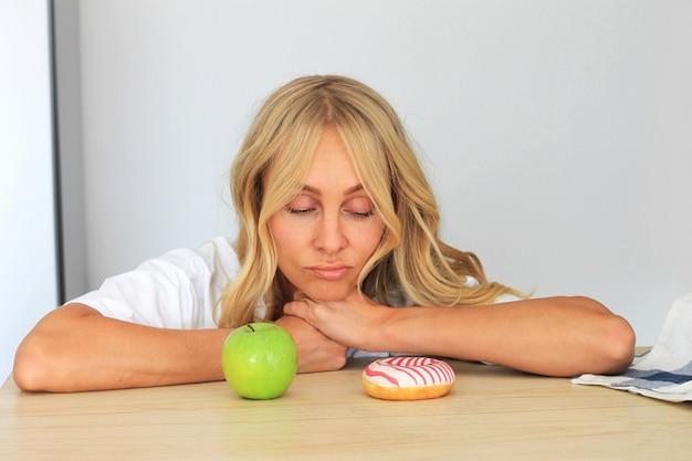 Vrouw die op doughnut op haar lijst kijkt, die zich tegen een verleiding verzet. Premium Foto