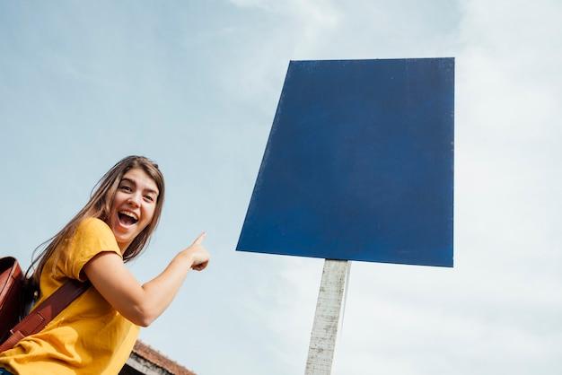 Vrouw die op een aanplakbordmodel richt Gratis Foto