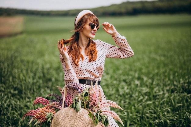 Vrouw die op een gebied met lupinuses loopt Gratis Foto