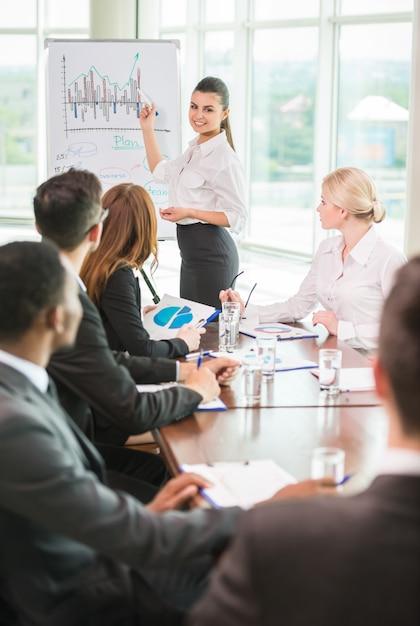 Vrouw die op een groeiende grafiek tijdens een vergadering richt. Premium Foto