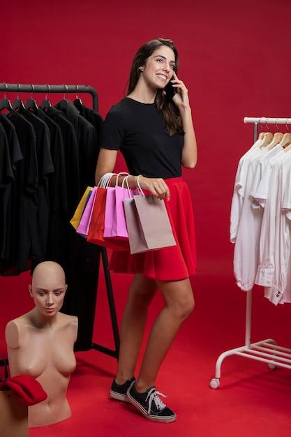 Vrouw die op haar telefoon bij het winkelen spreekt Gratis Foto