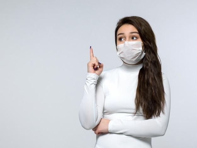 Vrouw die op haar vinger in witte kleding en wit medisch steriel beschermend masker wijst Gratis Foto