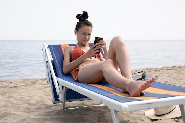 Vrouw die op ligstoel telefoon bekijkt Gratis Foto