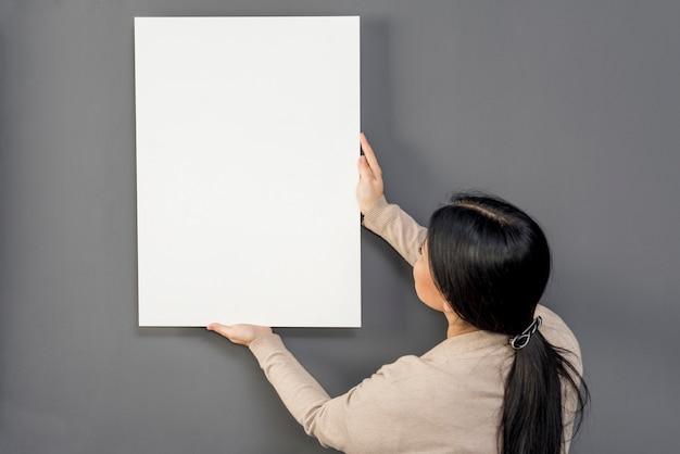Vrouw die op muur balnk document blad zet Gratis Foto