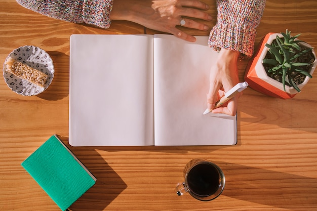 Vrouw die op pen met leeg wit notitieboekje over het houten bureau schrijft Gratis Foto