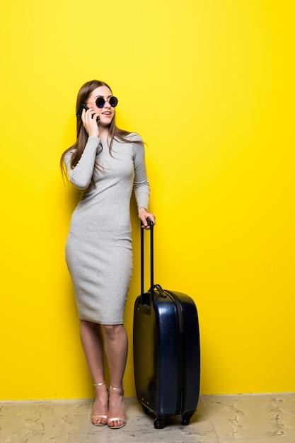 Vrouw die op reis gaat en op de telefoon over gele muur spreekt Gratis Foto
