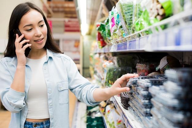Vrouw die op smartphone in supermarkt spreekt Premium Foto