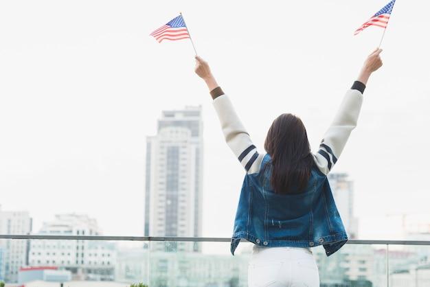 Vrouw die op stad en zwaaiende amerikaanse vlaggen kijkt Gratis Foto