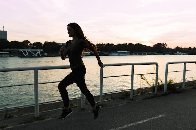 Vrouw die op straat bij zonsondergang loopt Gratis Foto