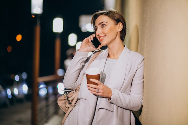 Vrouw die op telefoon en het drinken koffie buiten in de straat bij nacht spreken Gratis Foto