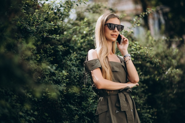Vrouw die op telefoon in park spreekt Gratis Foto