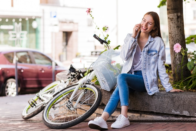 Vrouw die op telefoon naast fiets spreekt Gratis Foto
