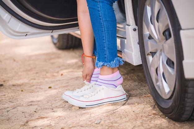 Vrouw die op tennisschoenen in auto aan de kant van de weg zet Premium Foto