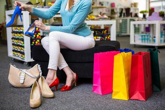 Vrouw die op verschillende schoenen probeert Premium Foto