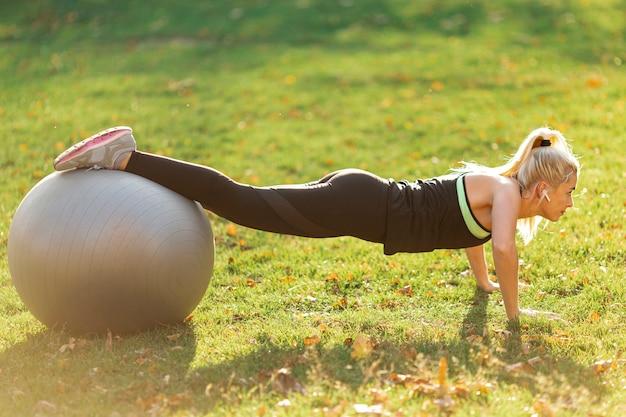Vrouw die opdrukoefeningen doet die gymnastiekbal gebruiken Gratis Foto