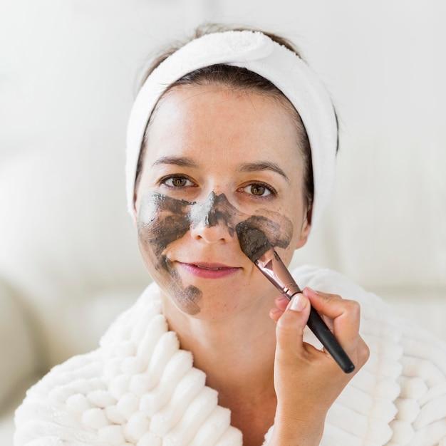 Vrouw die organische gezichtscrème met samenstellingsborstel toepast Gratis Foto