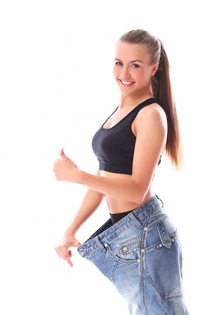 Vrouw die oude jeans na gewichtsverlies draagt Gratis Foto