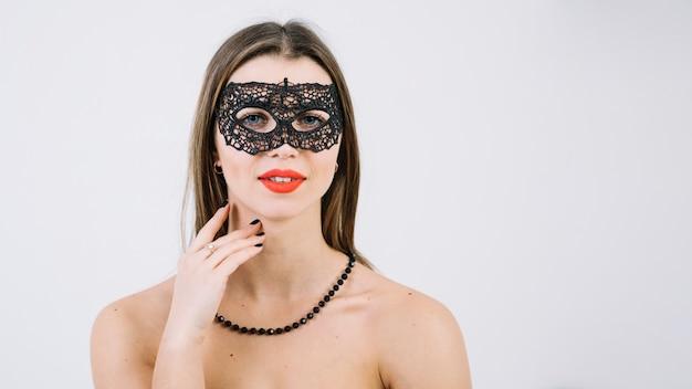 Vrouw die parelshalsband draagt in het masker die van maskeradecarnaval camera bekijken Gratis Foto