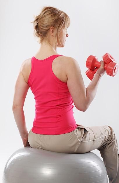 Vrouw die pilates en saldooefeningen met grijze bal doet Gratis Foto