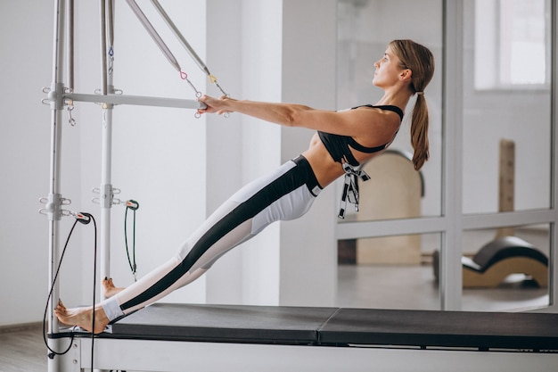 Vrouw die pilates in een pilateshervormer praktizeren Gratis Foto