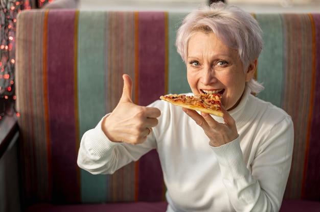 Vrouw die pizza eet die ok teken toont Gratis Foto