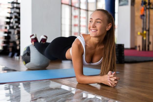 Vrouw die planken in gymnastiek doet Gratis Foto