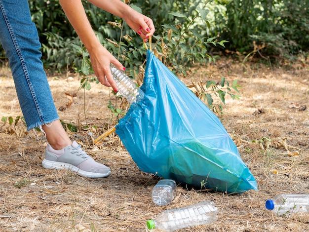 Vrouw die plastic flessen in zak voor recycling verzamelt Gratis Foto