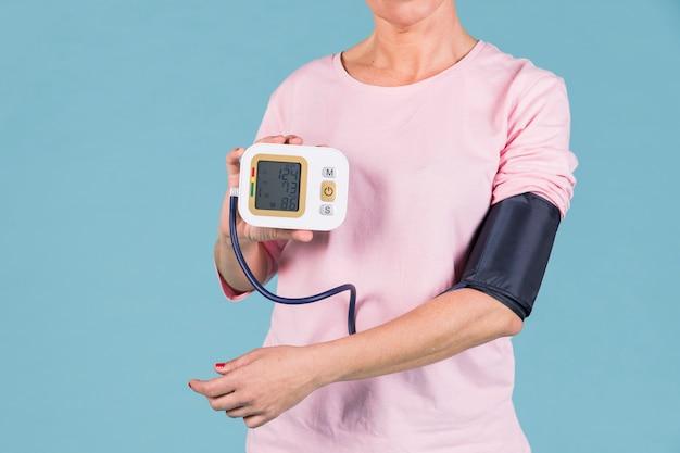 Vrouw die resultaten van bloeddruk op het elektrische tonometerscherm toont Gratis Foto