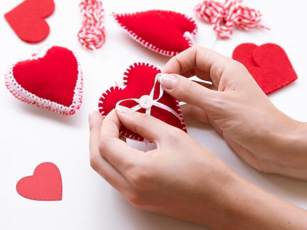 Vrouw die rode hartendecoratie maakt Gratis Foto