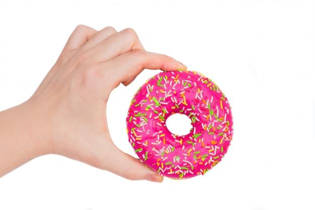 Vrouw die roze doughnut op witte achtergrond houdt. roze donut in de hand Premium Foto