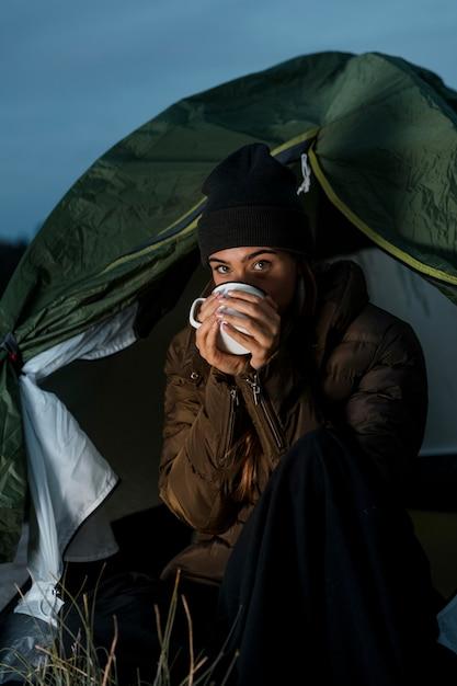 Vrouw die 's nachts kampeert met een kopje thee Gratis Foto
