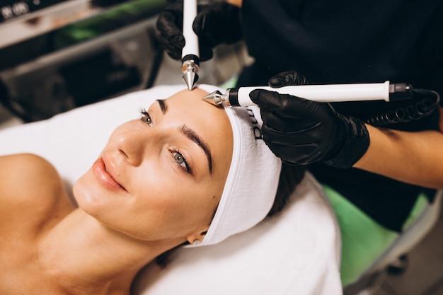 Vrouw die schoonheidsprocedures maken bij een schoonheidssalon Gratis Foto
