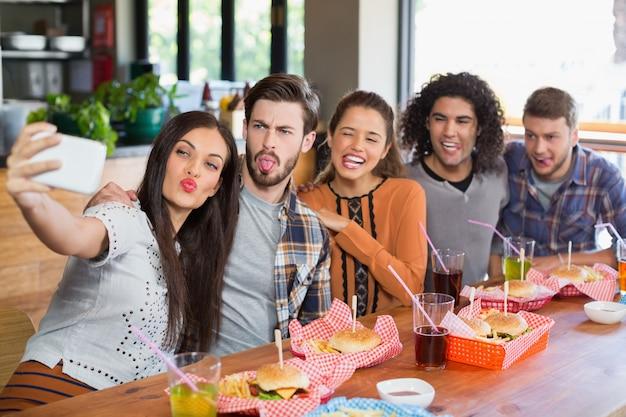Vrouw die selfie met vrienden in restaurant Premium Foto