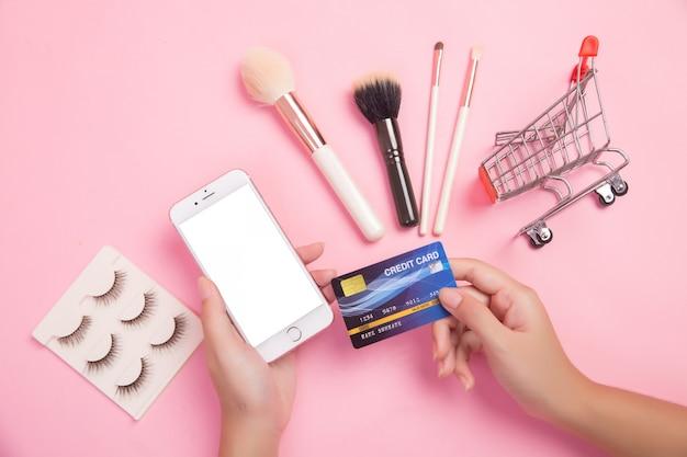 Vrouw die smartphone en creditcard het winkelen schoonheidspunten gebruiken Gratis Foto
