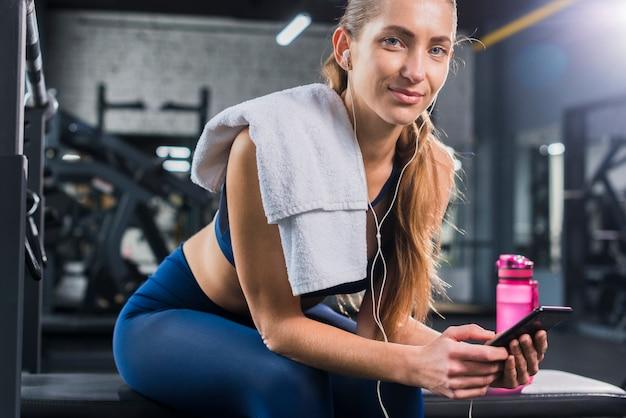 Vrouw die smartphone in gymnastiek gebruikt Gratis Foto