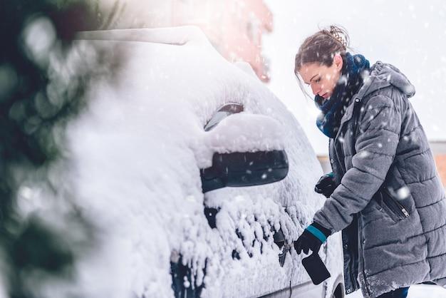 Vrouw die sneeuw behandelde auto ontsluiten Premium Foto