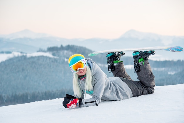Vrouw die snowboarder in openlucht liggend op de sneeuw ontspannen die aan de camera glimlachen Premium Foto