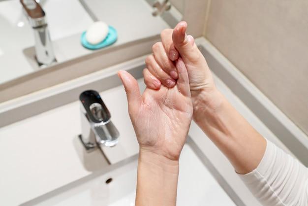 Vrouw die stappen volgt om goed met zeep te wassen en handen te ontsmetten en te desinfecteren. reinigingsmaatregelen tegen de verspreiding van virale covid 19-ziekte. coronavirus, gezondheids- en hygiëneconcept. Premium Foto